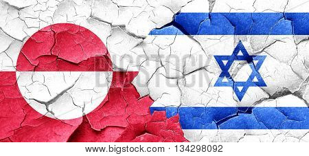 greenland flag with Israel flag on a grunge cracked wall