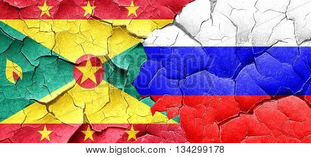 Grenada flag with Russia flag on a grunge cracked wall
