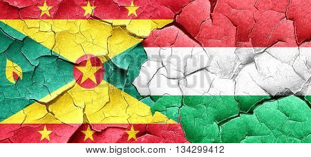 Grenada flag with Hungary flag on a grunge cracked wall