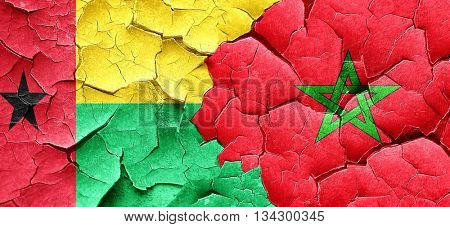Guinea bissau flag with Morocco flag on a grunge cracked wall