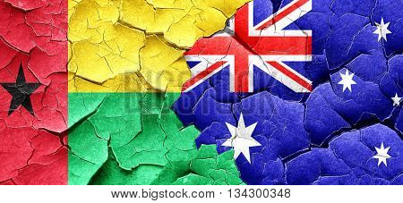 Guinea bissau flag with Australia flag on a grunge cracked wall