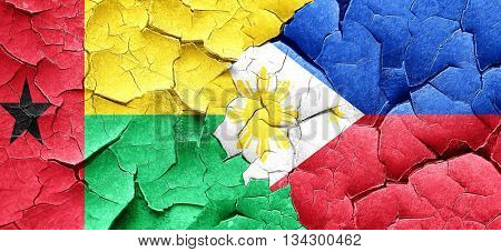 Guinea bissau flag with Philippines flag on a grunge cracked wal