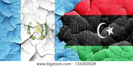 guatemala flag with Libya flag on a grunge cracked wall