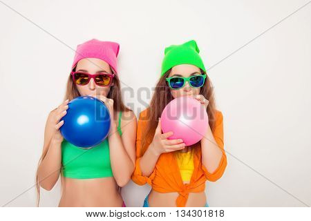 Portrait Of Two Hipster Girls In Glasses Blowing Balloons
