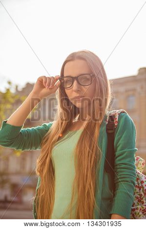 Portrait Of Long-haired Attractive Girl In Glasses With Backpack