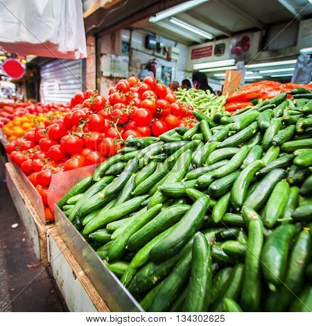 Countertop with vegetables stacked pile. Showcase with tomatoes and cucumbers in the Mahane Yehuda Market. Jerusalem. Israel.