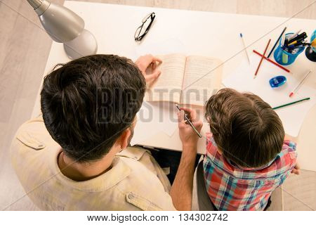 Top View Of Dad Helping His Son With Home Task