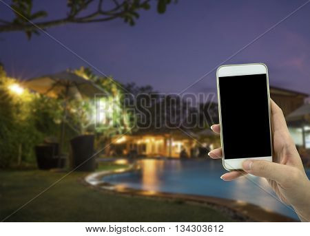 Female Hand Holding Smart Phone Over Blured Background