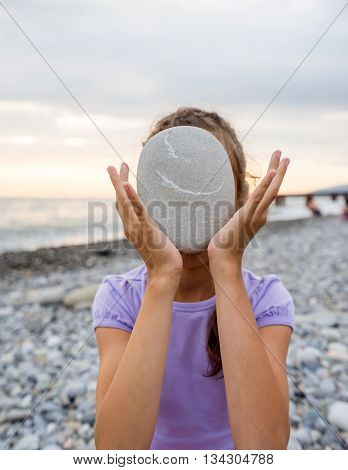 Young girl holding marine flat stone in front of face on background of the sea coast
