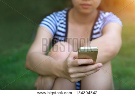 Focus hand of Young asian woman touching smartphone Young female use smartphone for chat and surfing the Internet - Sunset filter effect