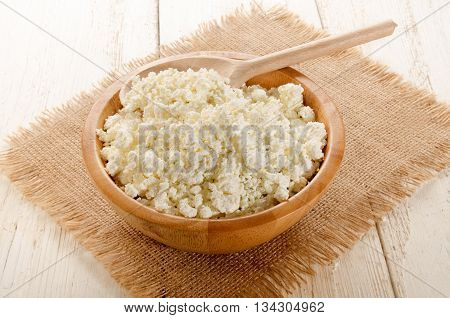 fresh home made cottage cheese with wooden spoon in a wooden bowl