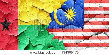 Guinea bissau flag with Malaysia flag on a grunge cracked wall