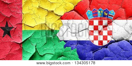 Guinea bissau flag with Croatia flag on a grunge cracked wall