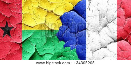 Guinea bissau flag with France flag on a grunge cracked wall
