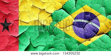 Guinea bissau flag with Brazil flag on a grunge cracked wall