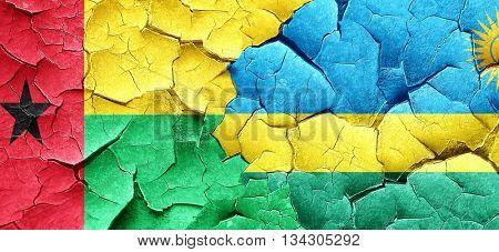 Guinea bissau flag with rwanda flag on a grunge cracked wall