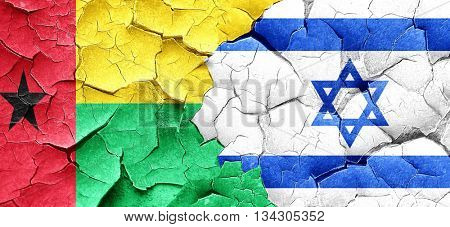 Guinea bissau flag with Israel flag on a grunge cracked wall