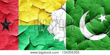 Guinea bissau flag with Pakistan flag on a grunge cracked wall