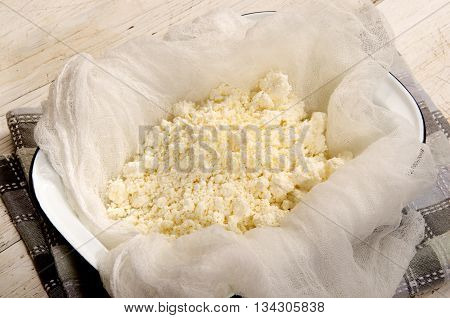 fresh home made cottage cheese with white towel in a blue and white enamel bowl