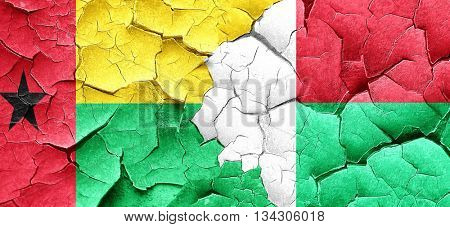 Guinea bissau flag with Madagascar flag on a grunge cracked wall