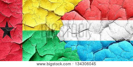 Guinea bissau flag with Luxembourg flag on a grunge cracked wall