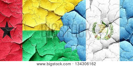 Guinea bissau flag with Guatemala flag on a grunge cracked wall