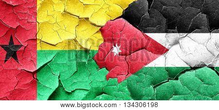 Guinea bissau flag with Jordan flag on a grunge cracked wall