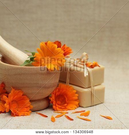 Alternative medicine background with calendula flowers and bath soap