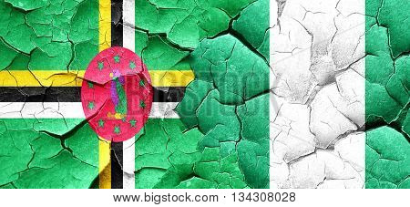 Dominica flag with Nigeria flag on a grunge cracked wall