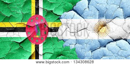 Dominica flag with Argentine flag on a grunge cracked wall