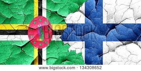 Dominica flag with Finland flag on a grunge cracked wall