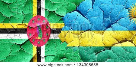 Dominica flag with rwanda flag on a grunge cracked wall