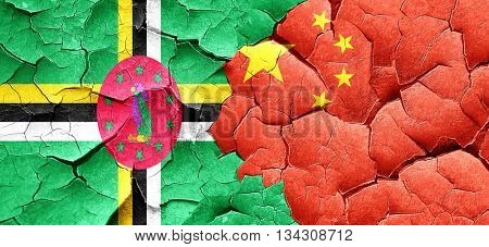 Dominica flag with China flag on a grunge cracked wall