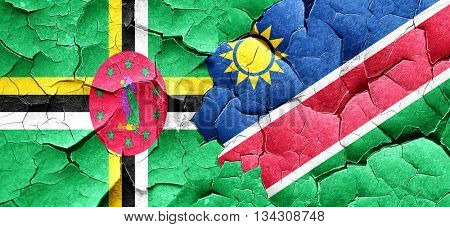Dominica flag with Namibia flag on a grunge cracked wall