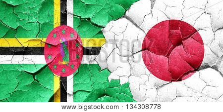 Dominica flag with Japan flag on a grunge cracked wall