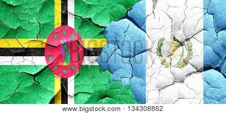 Dominica flag with Guatemala flag on a grunge cracked wall