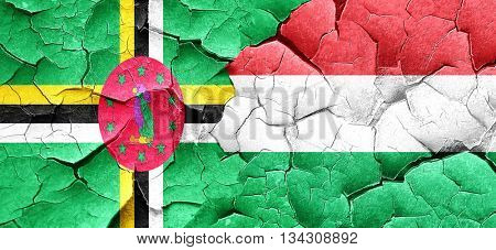 Dominica flag with Hungary flag on a grunge cracked wall