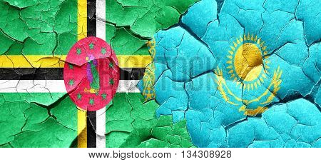 Dominica flag with Kazakhstan flag on a grunge cracked wall