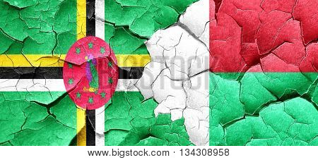 Dominica flag with Madagascar flag on a grunge cracked wall