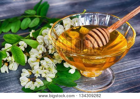 Honey honey dipper with acacia flowers on a dark wooden background