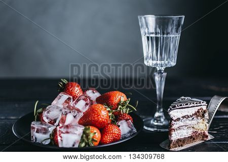 Plate of ice fresh strawberries and piece of cake shot over grey concrete background with glass of drink