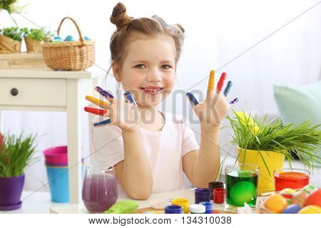 Little girl with painted fingers at home