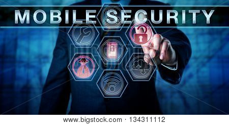 Male software developer touching MOBILE SECURITY on an interactive visual control screen. Business risk metaphor and cyber security concept for privacy protection of cell phone networks and devices.