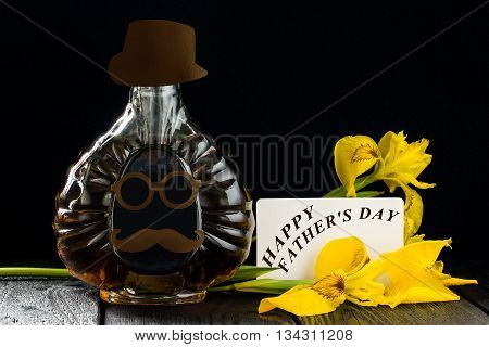 Fathers Day composition. Bottle with homemade fun applique in the shape of the face iris flowers and card with the words Happy Fathers Day