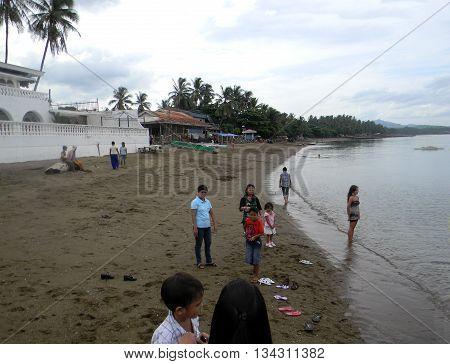 CEBU CITY, CEBU / PHILIPPINES - JULY 30, 2011: People enjoy the sand and water at a public beach in Cebu.