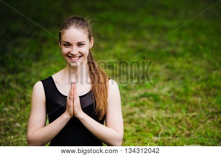 Young yoga teacher practicing outdoors in a park over green grass with copy space.