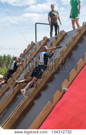 Tyumen Russia - June 11 2016: Race of Heroes project on the ground of the highest military and engineering school. Athlete gets on inclined wall by means of bar