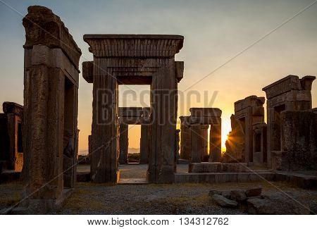 Beautiful Sunset with warm orange glow behind ruins of Tachara Palace or Palace of Darius from Achaemenid Empire in Persepolis of Shiraz.