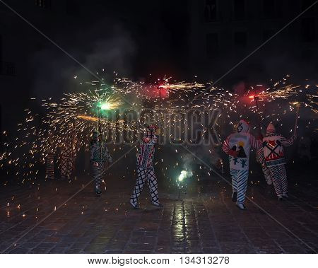 Correfocs (fire runs) or Baile de Diablos (Devils' Dance) - essential part of tradition originating from Catalonia. Group of people dressed as devils and dancing with lighting fireworks. Reus Spain.