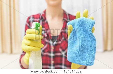 Woman wash that something spray and cloth. Focus on the spray.